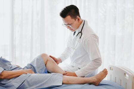 Ujęcie lekarza traumatologa badającego jego kolano pacjenta na łóżku w szpitalu