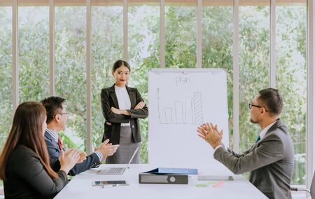Great and success presentation, young confident Asian woman standing near flipboard and smiling while her colleagues sitting at the desk and applauding in meeting room