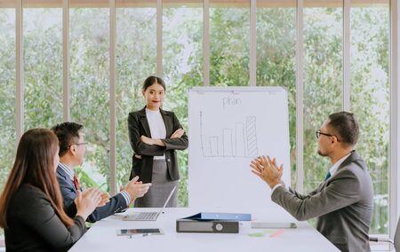 Presentación excelente y exitosa, joven asiática confiada de pie cerca de flipboard y sonriendo mientras sus colegas sentados en el escritorio y aplaudiendo en la sala de reuniones