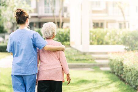 Rückansicht der Pflegekraft, die mit einer älteren Frau im Freien geht