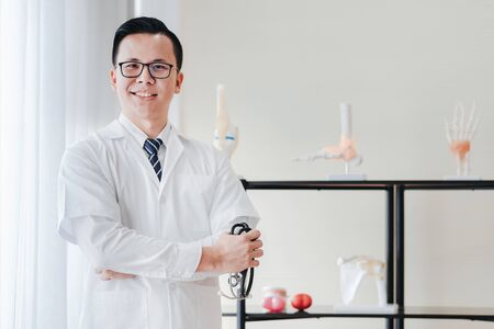 Friendly Asian doctor smiling with arms crossed holding stethoscope in hand at hospital in his office