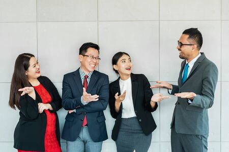 Happy group of Asian business people smiling and laughing in their office. Teamwork and business success concept