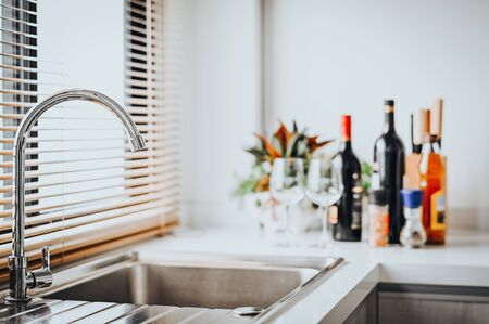 Close up shot of stainless steel faucet in a modern kitchen with bottle of wine in background