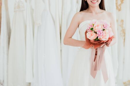 Cropped shot of happy pretty happy bride in wedding dress with bouquet of roses in hand