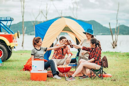 Group of young Asian friends having barbecue and clinking bottle of beers while camping by the lake- Happy people enjoying outdoor travel.