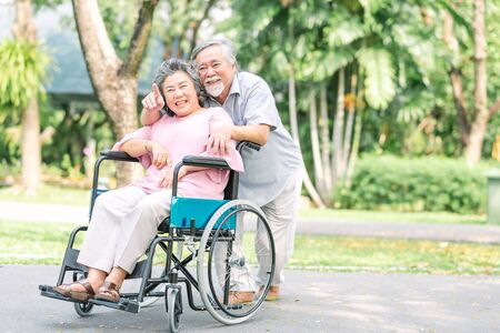 Happy smiling Asian senior woman in a wheelchair relaxing and walking with her husband outside at the park. Senior couple happy lifestyle.