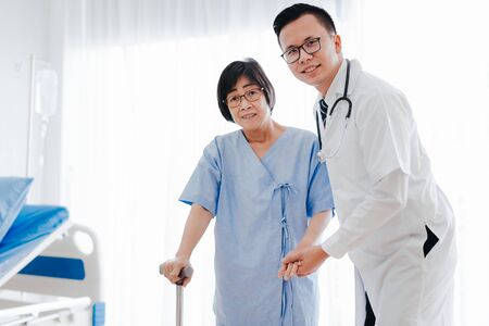 Asian man doctor help and support senior woman patient walking with a cane in hospital