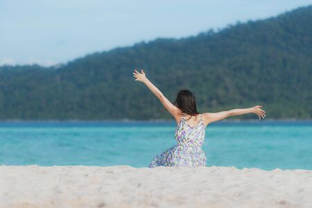 Back view of Asian woman enjoying travel at the sea with open arms freedom pose on the beach. Summer vacation concept Stock fotó