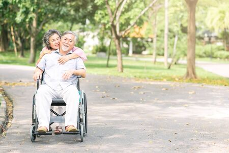 Happy smiling Asian senior woman hugging her husband in wheelchair from behind outside at the park. Senior couple happy lifestyle
