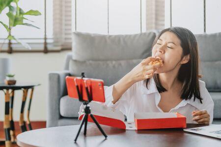 Bloguera de comida asiática comiendo pizza mientras crea un nuevo video de contenido para su canal usando un teléfono inteligente. Blogger de reseñas de alimentos.