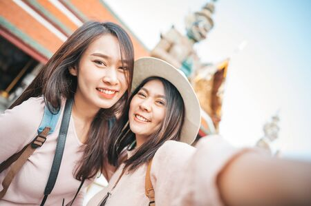 Happy young tourist women enjoy taking selfie together in temple of the emerald buddha, Wat Phra Kaew, popular tourist place in Bangkok, Thailand