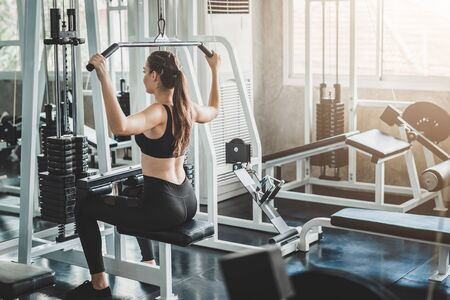 Back view of healthy young caucasian woman doing lat pull pull down exercise in fitness gym Reklamní fotografie
