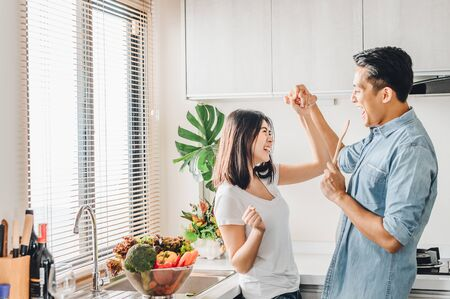 Romantic Asian couple in love is dancing and smiling while cooking together in kitchen