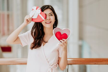 Beautiful happy smiling and cheeful Asian woman holding gift box with red heart inside on valentine day having fun