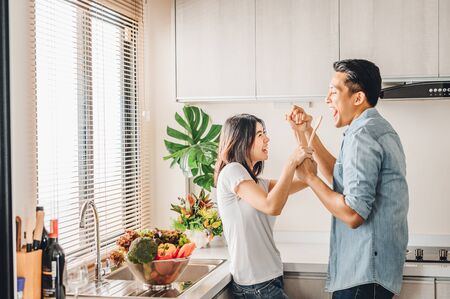 Romantic Asian couple in love is singing and dancing while cooking together in kitchen