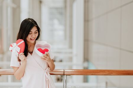 Beautiful happy smiling and cheeful Asian woman holding gift box with red heart inside on valentine day Zdjęcie Seryjne