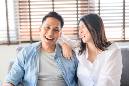 Portrait of happy Asian couple in love smiling and laughing  having a good time together on sofa at home Zdjęcie Seryjne