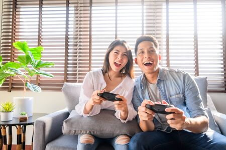 Happy Asian couple using joystick controller playing video games together while sitting on sofa  in their living room