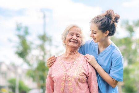 Lächelnde Krankenschwester kümmert sich um asiatische ältere Frau im Freien im Park