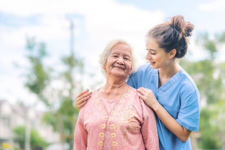 Smiling nurse caregiver take care of Asian elderly woman outdoor in the park