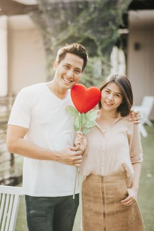 Romantic happy Asian couple in love holding heart shape flower. Vanlentine day concept.