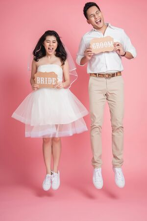 Happy Asian bride and groom in casual wedding dress jumping make funny face with eye close over pink background