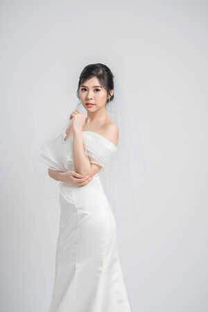 Portrait of beautiful young Asian bride in wedding dress on grey background