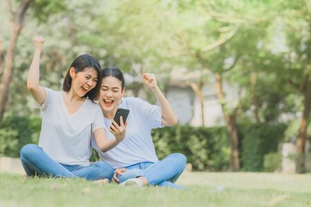 Happy asian women best friends celebrating success holding mobile phone sitting on grass in the park
