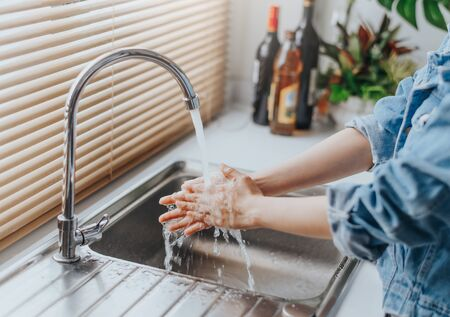 Close up shot of woman washing hands in sink at home kitchen