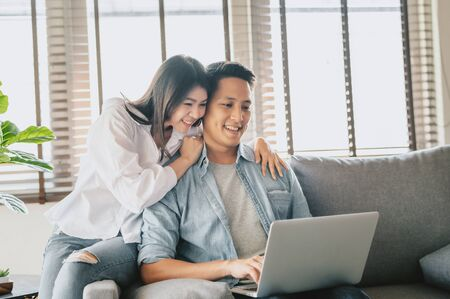 Happy Asian couple using laptop on sofa at home. Woman embracing man from behind 스톡 콘텐츠