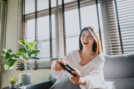 Excited Asian woman looking at tv screen and holding controller while playing video game at home in living room 스톡 콘텐츠