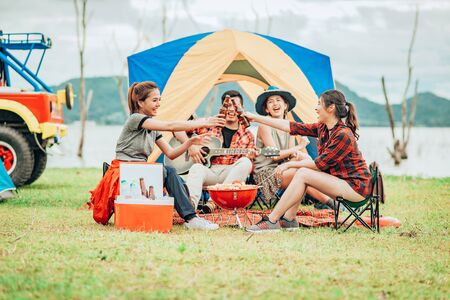 Two Asian women toasting bottles of beer to each other to celebrate a good time with a group of friends while traveling on a camping tent on holiday.