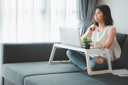 Asian woman thinking while working with laptop notebook at home on sofa  스톡 콘텐츠