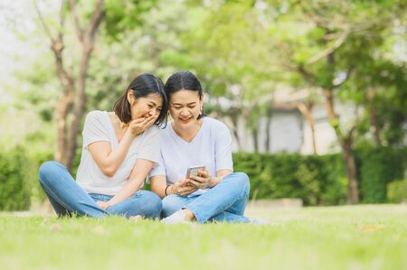 Two happy best friends Asian women are laughing while using mobile smartphone outdoor in the park.