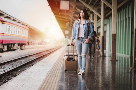 beautiful smiled Asian tourist woman walking with luggage on the platform at the train station during travel vacation
