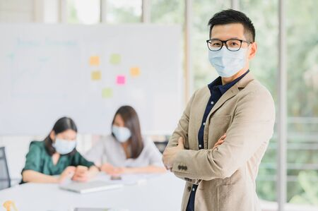 Happy Asian man entrepreneur wears face mask standing arms crossed with confident, with a colleague in background in meeting room at modern office Banque d'images