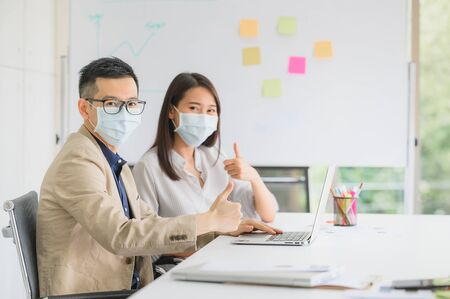 Happy Asian businessman and woman wear face mask showing thumb up with confident in meeting room at modern office
