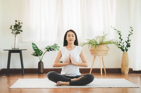 Shot of attractive healthy Asian woman doing yoga meditation at home in living room Foto de archivo