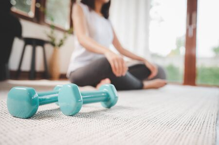 Pair of dumbbell on the living room floor with woman doing meditation in background