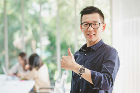 Happy Asian businessman smiling with thumbs up gesture with colleague in background in meeting room Banco de Imagens