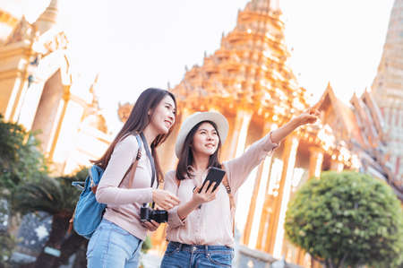 Tourist women enjoy travel in temple of the emerald buddha, Wat Phra Kaew popular tourist place in Bangkok, Thailand, checking for direction