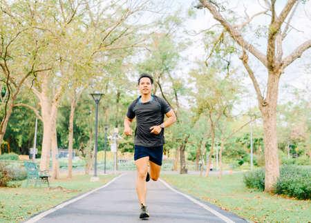 Happy healthy Asian man runner running outdoor in the park in morning