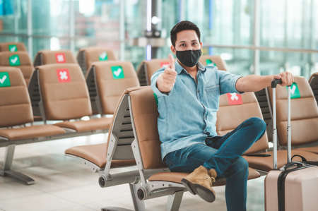 Traveler Asian man with luggage wearing mask protect from coronavirus sitting on social distancing chair showing thumb up with confident Reklamní fotografie