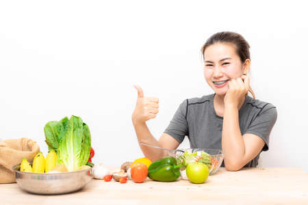Happy Asian woman with detal braces holding banana on white background