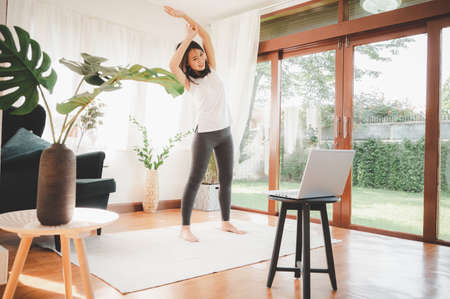 Happy Asian woman learned online workout stretching exercise fitness class at home from laptop. Self isolation and workout at home