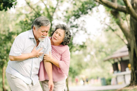 Senior Asian man holding his chest and feeling pain suffering from heart attack while his wife giving support and help outdoor at the park