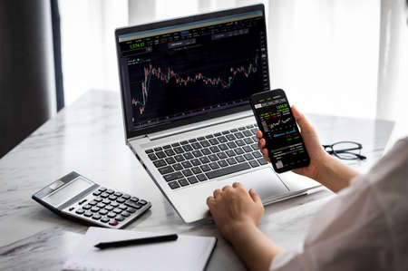 Hand holding smartphone with stock market data and using laptop display graph and chart for analyze. Online investment concept