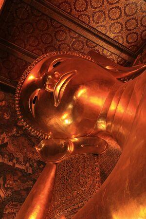 Reclining Buddha gold statue face  Wat Pho, Bangkok, Thailand photo