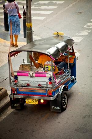 silom: BANGKOK - JUN 17, 2013: A three-wheeled tuk tuk taxi Waiting passengers in Silom road. The central business district of Bangkok on JUN 17, 2013, in Bangkok Thailand,