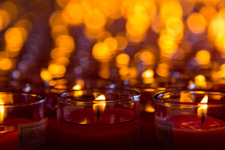 black worship: Church candles in red transparent chandeliers